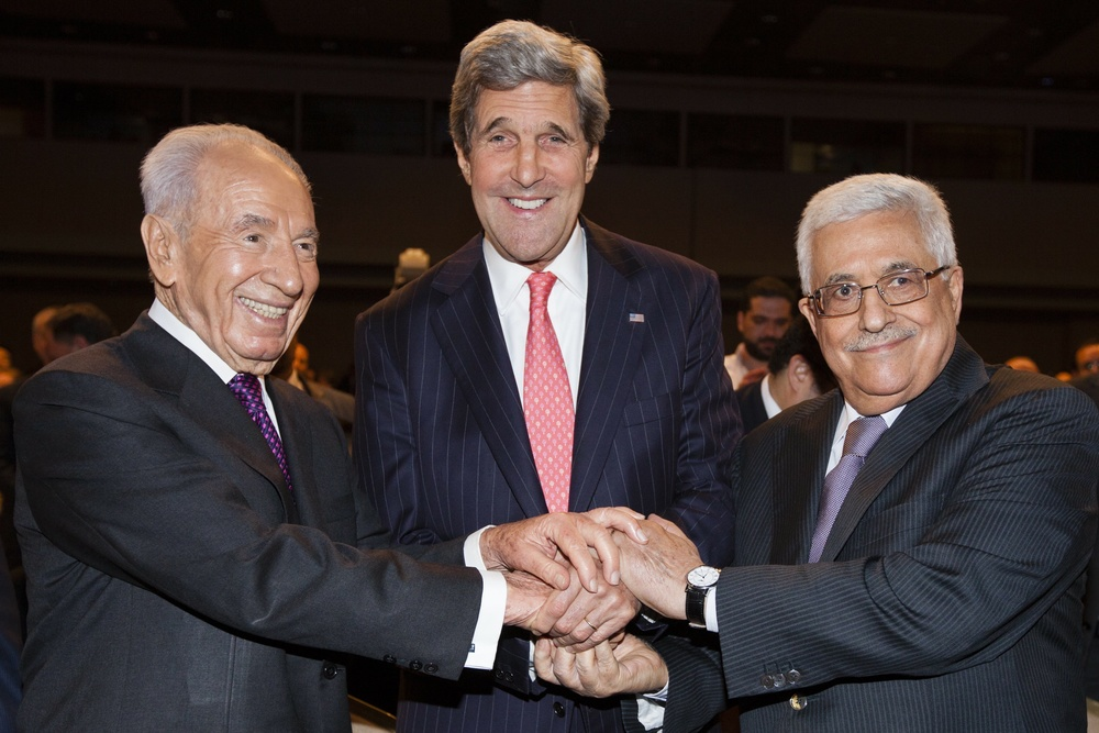 "Click photo to download. Caption: From left to right: Israeli President Shimon Peres, U.S. Secretary of State John Kerry, and Palestinian Authority President Mahmoud Abbas shake hands at the World Economic Forum on the Middle East and North Africa in Amman, Jordan, on May 26, 2013. Kerry on Friday announced an agreement on a ""basis"" for renewed Israeli-Palestinian conflict talks. Credit: Flash90."