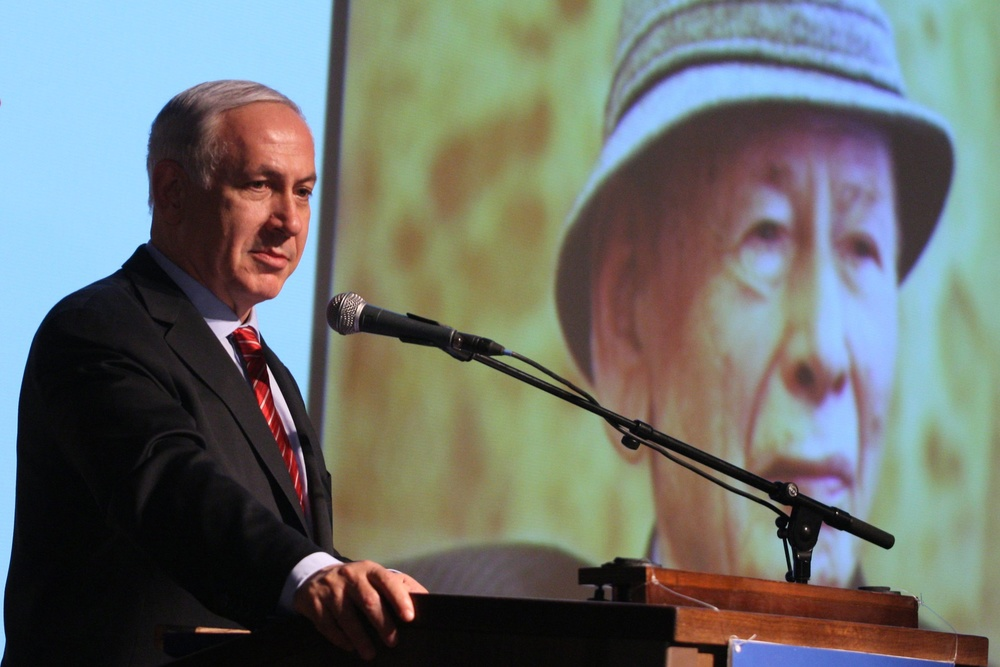 Click photo to download. Caption: Israel's Prime Minister Benjamin Netanyahu speaks at the screening of a movie about his father Benzion (pictured on screen) at the Begin Center in Jerusalem, May 28, 2012. Credit: Alex Kolomoisky/POOL/Flash90.