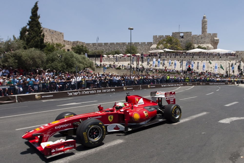 Click photo to download. Caption: Formula One Scuderia Ferrari team driver Giancarlo Fisichella drives a Ferrari F60 past The Tower of David and the ancient walls of Jerusalem's Old City, during the second day of the Jerusalem Formula Peace Road Show, on June 14, 2013. The first-ever two-day Jerusalem Formula Peace Road Show includes Formula One racing teams, Scuderia Ferrari and Marussia, Ferrari Challenge cars, drifting cars and Grand Prix motorcycles all participating in the show, whose circuit passes landmarks such as Jerusalem's Old City walls.