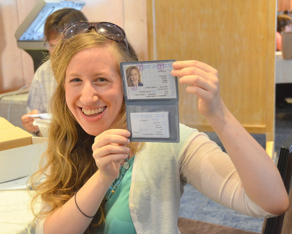 Click photo to download. Caption: Jessie Oppenheimer, a recent graduate of Yale University, smiles with her teudat zehut (Israeli identity document) in Jeruslem at a resource fair organized by the Nefesh B'Nefesh aliyah organization. Credit: Maxine Dovere.