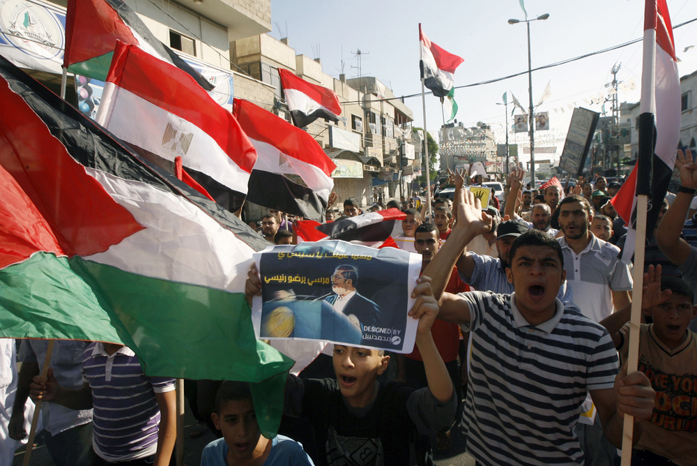 """Click photo to download. Caption: Palestinians gather during a demonstration in support of ousted Egyptian President Mohamed Morsi in the Hamas-controlled southern Gaza Strip town of Rafah on August 23, 2013. The removal of Morsi—a president from Hamas's parent group, the Muslim Brotherhood—creates """"serious problems for Hamas,"""" Matthew Levitt of the Washington Institute for Near East Policy said. Credit: Abed Rahim Khatib/Flash 90."""