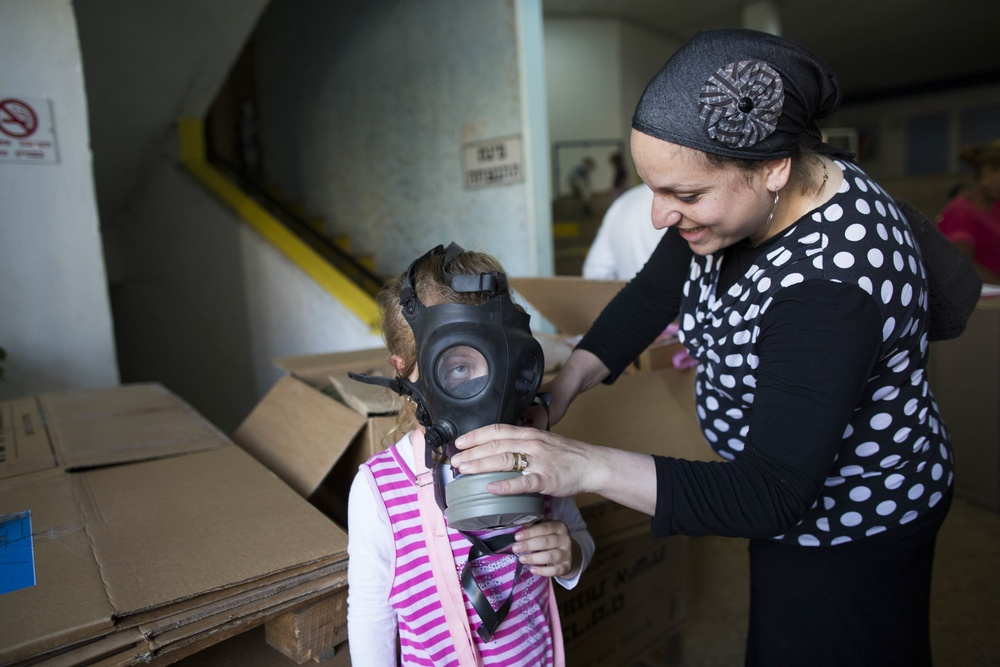 Click photo to download. Caption: An Israeli woman shows her child how to put on a gas mask at a distribution center in Jerusalem on August 27, 2013. As talks of an international attack on Syria heighten, the demand for gas masks in Israel rose. Credit: Yonatan Sindel/Flash90.