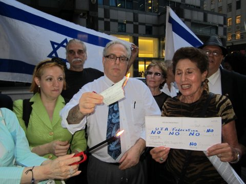 Richard Allen (center), head of JCC Watch, holds a burning check at a rally on Sept. 12 during which his group as well as Americans for a Safe Israel urged the cessation of Jewish donations to the UJA-Federation of New York, due to federation's lack of funding guidelines on Israel. Credit: JCC Watch/AFSI.