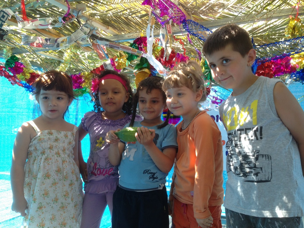 Maria (age 5) of Ukraine, Gavriel (age 5) of Yemen, Annamalai (age 5) of Peru, AJ (age 6) of South Africa, and Sofia (age 4) of Argentina—all of them recent immigrants to Israel—pose in the sukkah they helped build at The Jewish Agency's Ye'elim Immigrant Absorption Center in Be'er Sheva, Israel. Credit: Tali Nehama, The Jewish Agency for Israel.