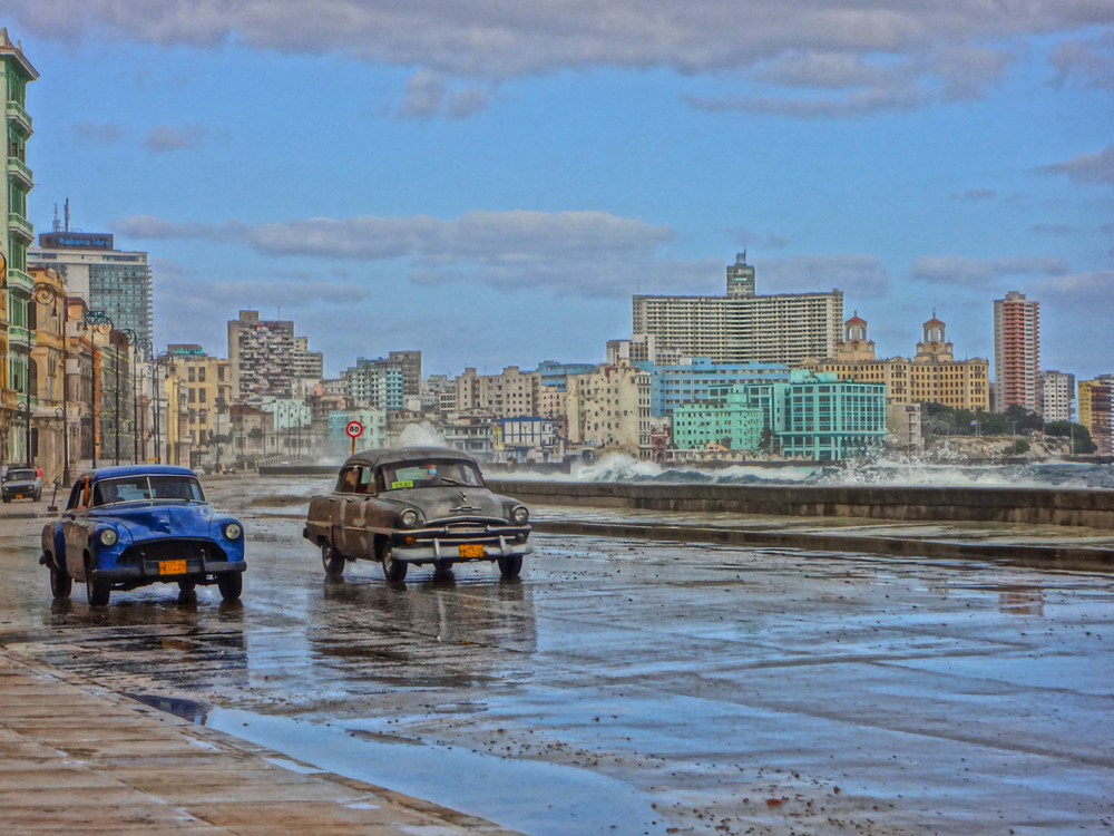 Click photo to download. Caption: Old American cars are a Cuban staple. Here they drive on a road bordering Havana Bay. Credit: Marla Whitesman/photo illustration.