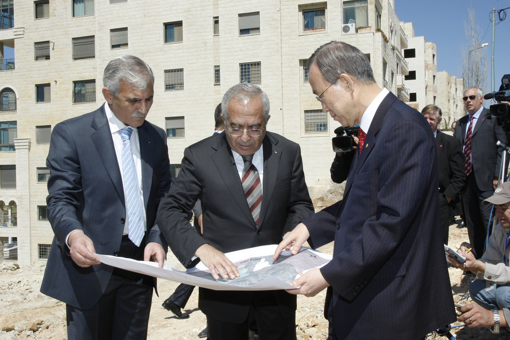 "Click photo to download. Caption: UN Secretary-General Ban Ki-moon (right) and Salam Fayyad (center), former Prime Minister of the Palestinian National Authority, look over a map during their visit to the West Bank's Area C, outside Ramallah. A new World Bank report, entitled ""Area C and the Future of the Palestinian Economy,"" blames Israel for shortcomings within the Palestinian economy. Credit: UN Photo/Mark Garten."