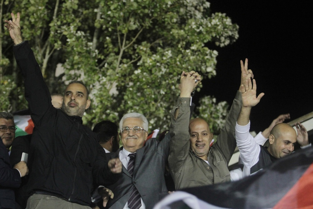 "Click photo to download. Caption: Palestinian Authority President Mahmoud Abbas (second from left) waves with released Palestinian prisoners coming from Israeli jails during celebrations at Abbas's headquarters in Ramallah, October 30, 2013. Abbas at the celebration called freed terrorist prisoners ""heroes,"" Palestinian Media Watch  reported at the time. Credit: Issam Rimawi/FLASH90."