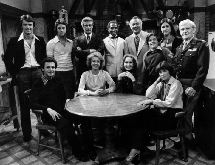 "Click photo to download. Caption: Billy Crystal—sitting, far left—on the cast of ""Soap"" in 1977. Credit: ABC Television via Wikimedia Commons."