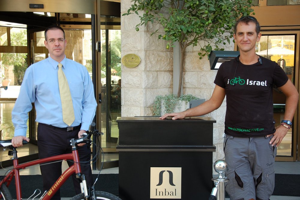 Click photo to download. Caption: Inbal Hotel Communications Manager Barak Roth (left) and Amir Rockman, bicycle director of Israeli tour operator Gordon Active, outside the Inbal in Jerusalem. Credit: Barry A. Kaplan.