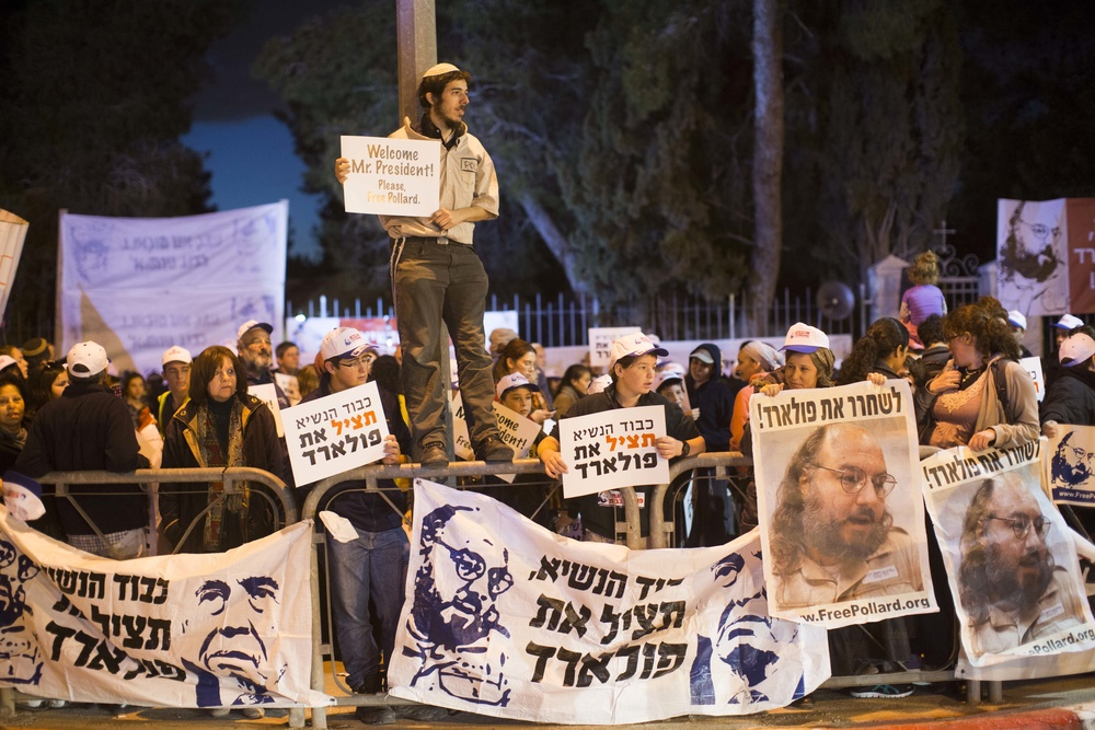 "Click photo to download. Caption: Israeli protesters holding placards reading ""Free Pollard"" and portraits of Jonathan Pollard during a protest calling for Pollard's release from U.S. prison outside Israeli President Shimon Peres's Jerusalem residence on March 19, 2013. Credit: Yonatan Sindel/Flash90."