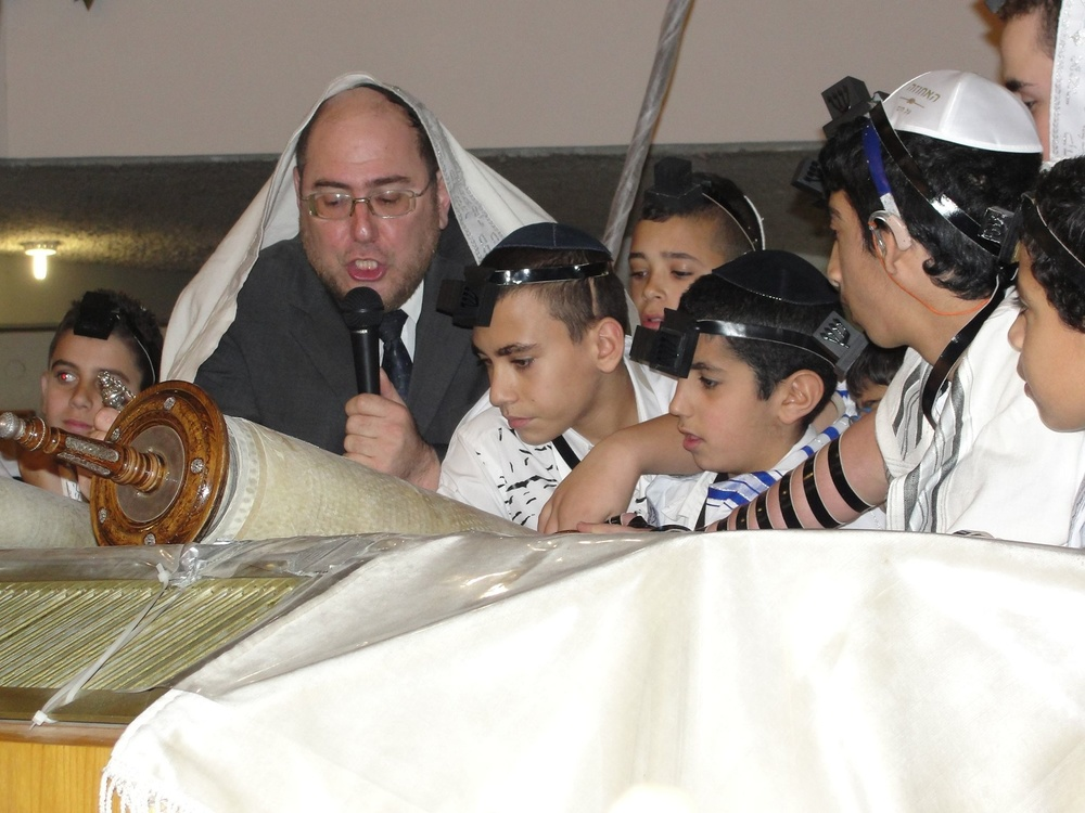 Click photo to download. Caption: Rabbi Chanoch Yeres, director of the Deaf Programming Division of International Young Israel Movement (IYIM), leads a 2013 bar mitzvah for 63 deaf and hard of hearing children. Credit: Judy Lash Balint.