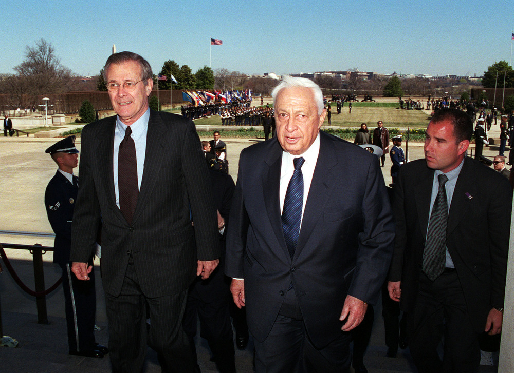 Click photo to download. Caption: U.S. Secretary of Defense Donald H. Rumsfeld (left) escorts Israeli Prime Minister Ariel Sharon (center) into the Pentagon at the conclusion of a full honor arrival ceremony for Sharon at the Pentagon on March 19, 2001. Credit: Robert D. Ward via Wikimedia Commons.