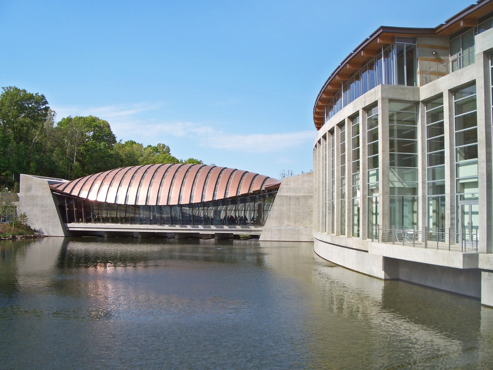 Click photo to download. Caption: The Crystal Bridges Museum of American Art in Bentonville, Arkansas, designed by Moshe Safdie. Credit: Charvex via Wikimedia Commons.