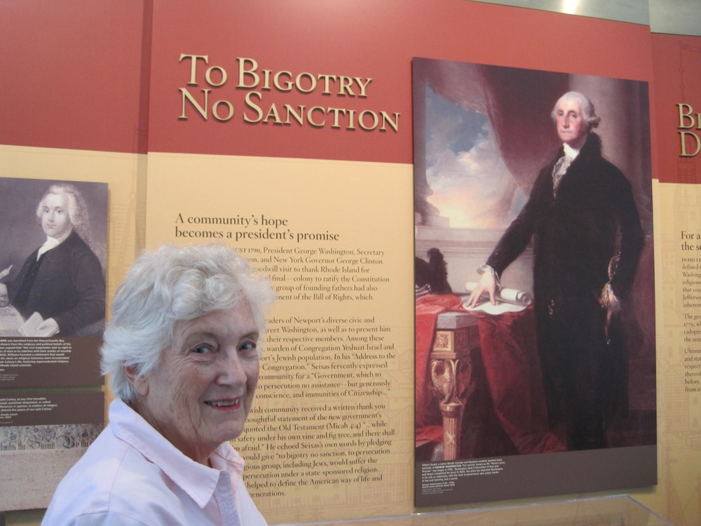 "Click photo to download. Caption: Rita Eisenberg Slom—a Newport, RI, native who served as president of the historic Touro Synagogue from 1999-2001—is pictured in the Ambassador John L. Loeb Jr. Visitors Center next to a poster of the famous letter President George Washington addressed ""To the Hebrew Congregation in Newport Rhode Island,"" which is read annually at Touro Synagogue. Credit: Paul Foer."