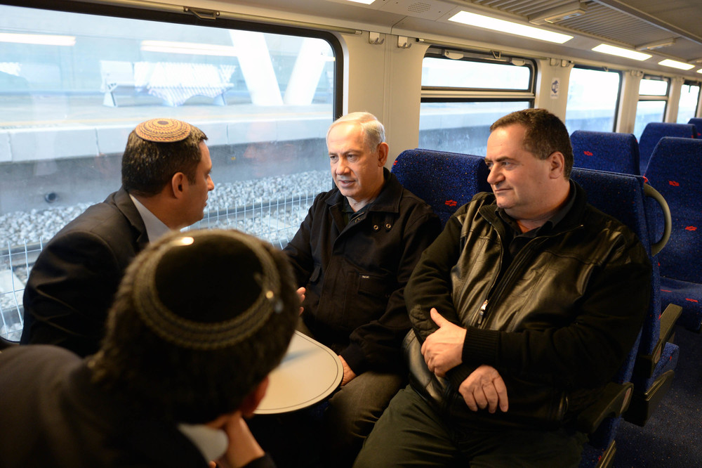 Click photo to download. Caption: Israeli Prime Minister Benjamin Netanyahu and Israeli Minister of Transportation Yisrael Katz seen aboard a train in the southern Israeli town of Sderot, where they inaugurated a new rocket-proof train station, on Dec. 24, 2013. The new train line connects isolated Negev communities to larger Israeli population centers. Credit: Kobi Gideon/GPO/Flash90.