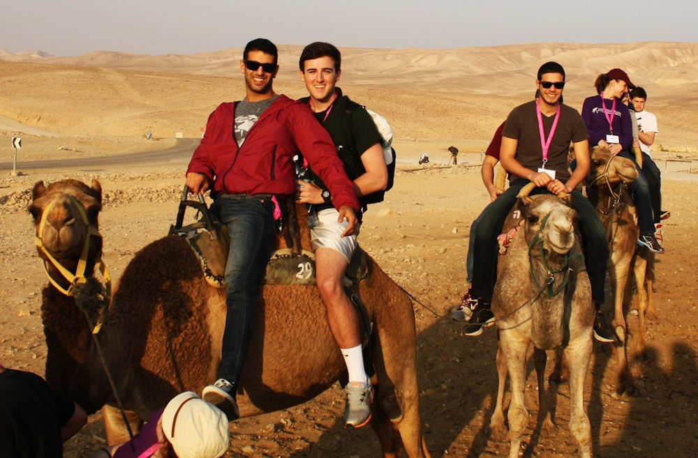 Participants ride camels during a Taglit-Birthright Israel trip through Hillel International. Credit: Photo courtesy of Hillel International.