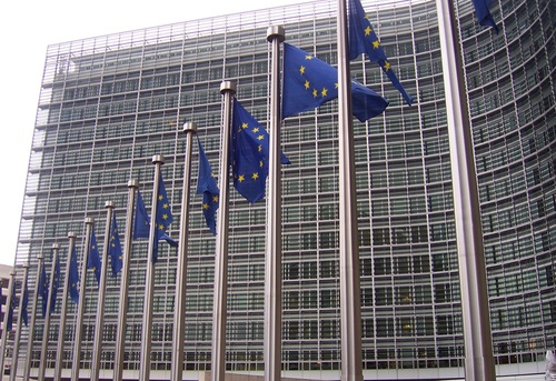Click photo to download. Caption: European Union (EU) flags in front of the<br />European Commission building in Brussels. Credit: Amio Cajander via<br />Wikimedia Commons.