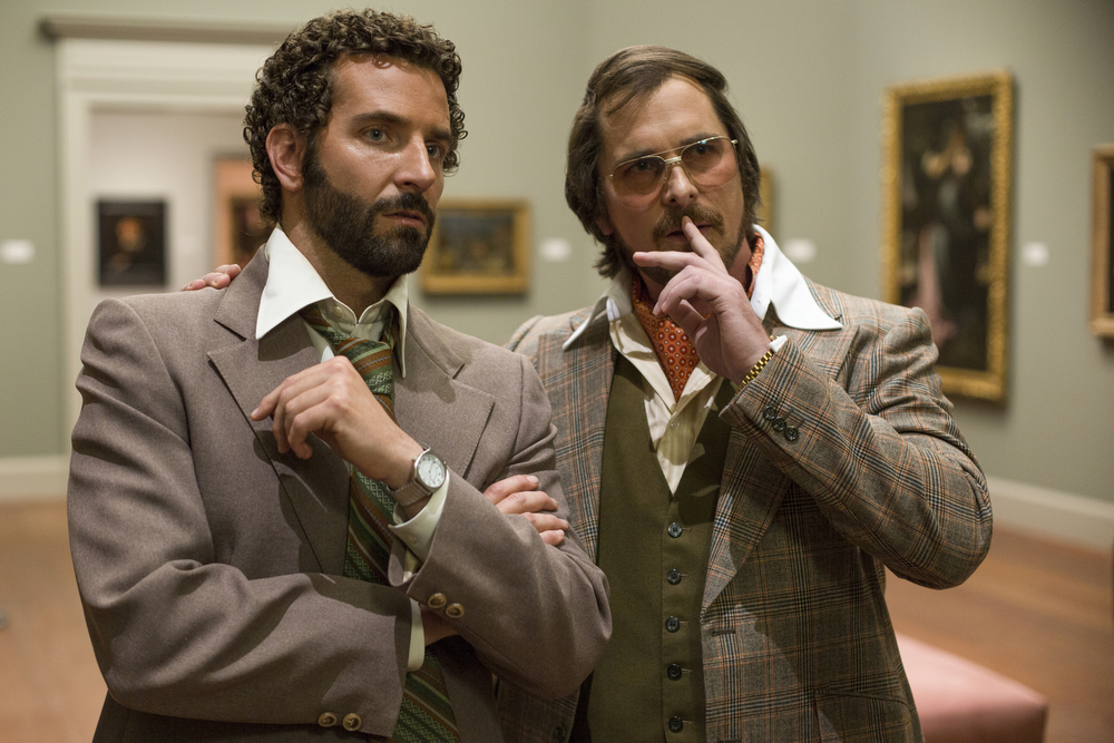 "Click photo to download. Caption: Bradley Cooper (left) as Richie DiMaso and Christian Bale as Irving Rosenfeld (a character based on the true story of Jewish con artist Melvin Weinberg) in the Oscar-nominated ""American Hustle."" Credit: Sony Pictures."