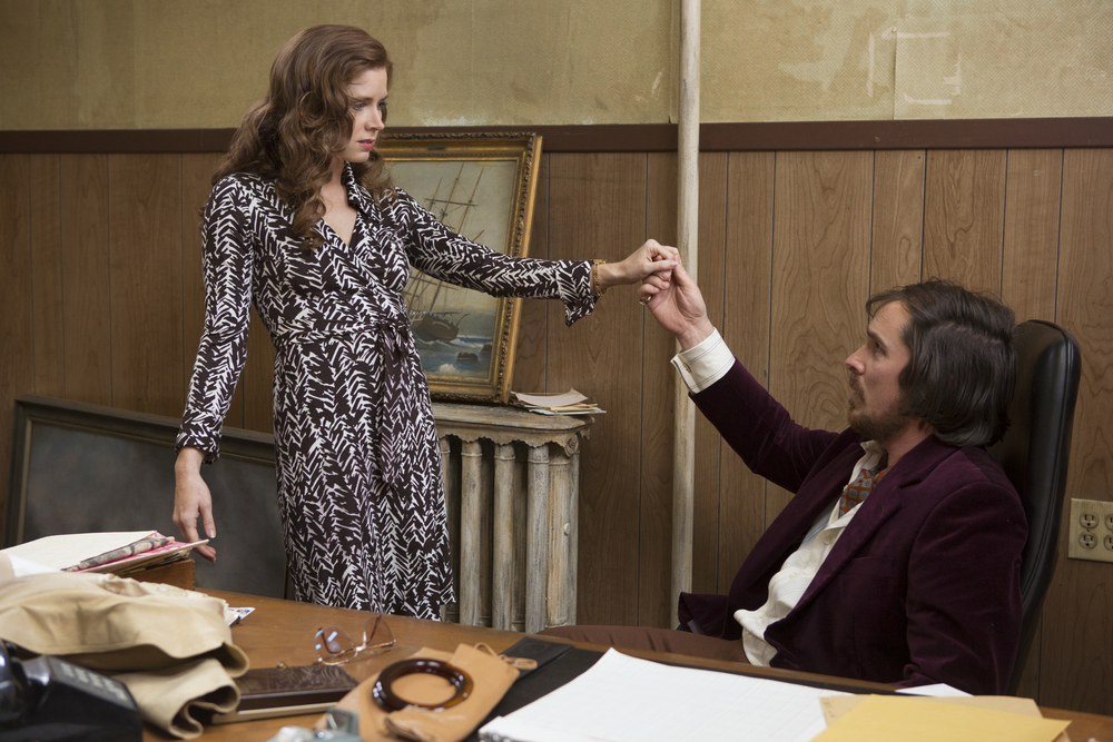"Click photo to download. Caption: Amy Adams as Sydney Prosser and Christian Bale as Irving Rosenfeld (a character based on the true story of Jewish con artist Melvin Weinberg) in the Oscar-nominated ""American Hustle."" Credit: Sony Pictures."