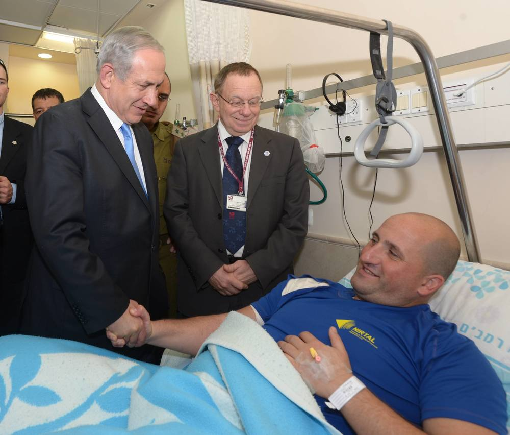 At Rambam Hospital in Haifa, Israeli Defense Minister Moshe Ya'alon and Prime Minister Benjamin Netanyahu visit a soldier wounded by an explosion on the Israel-Syria border on Tuesday. Credit: Amos Ben-Gershom/GPO.