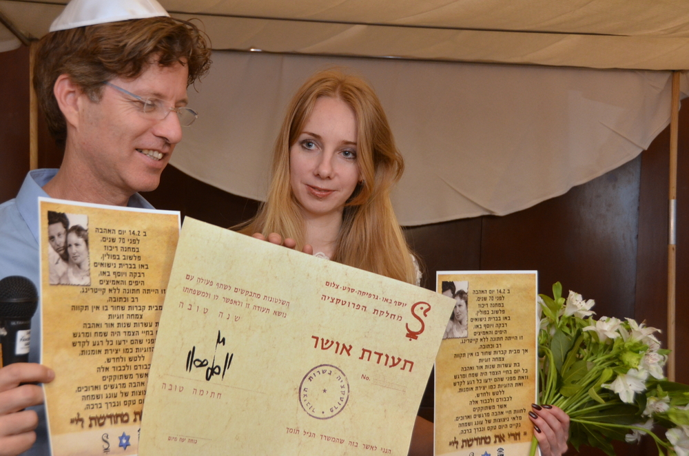"Click photo to download. Caption: Boaz Bau-Simon, the grandson of Joseph and Rebecca Bau, with his fiancé Or (Irena) Gatina in February 2014. The couple announced its engagement at the ceremony commemorating the 70th wedding anniversary of Bau-Simon's grandparents. Bau-Simon and Gatina are pictured holding a ""teudat osher"" (""certificate of happiness"") originally created by Joseph Bau as well as a letter relating the story of the lifelong romance of Joseph and Rebecca Bau. Credit: Maxine Dovere."