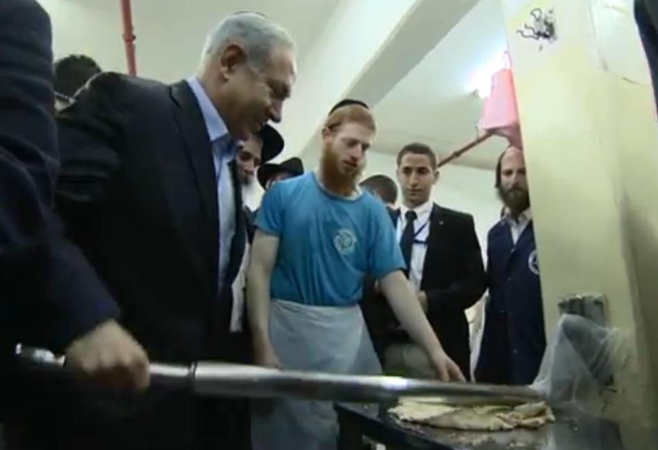 Prime Minister Benjamin Netanyahu bakes matzah on Tuesday. Credit: Israel Hayom video screenshot.