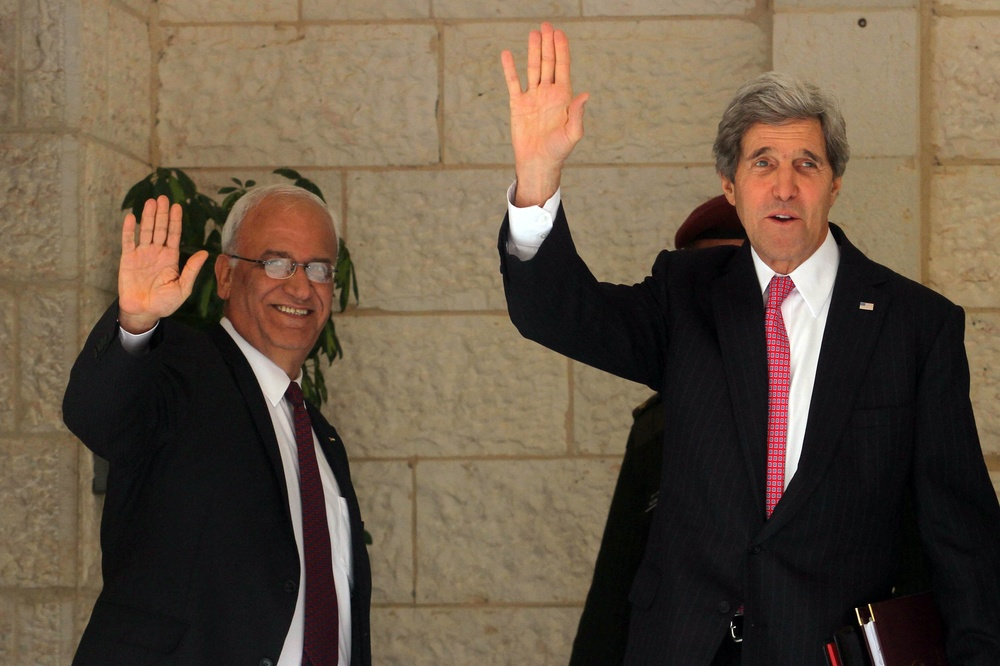 Click photo to download. Caption: U.S. Secretary of State John Kerry (right) and chief Palestinian negotiator Saeb Erekat wave before a meeting with Palestinian Authority President Mahmoud Abbas in Ramallah on Jan. 4, 2014. After recent developments, all parties involved may soon be waving goodbye to the Israeli-Palestinian peace negotiations, which have an April 29 deadline for a resolution. Credit: Issam Rimawi/Flash90.