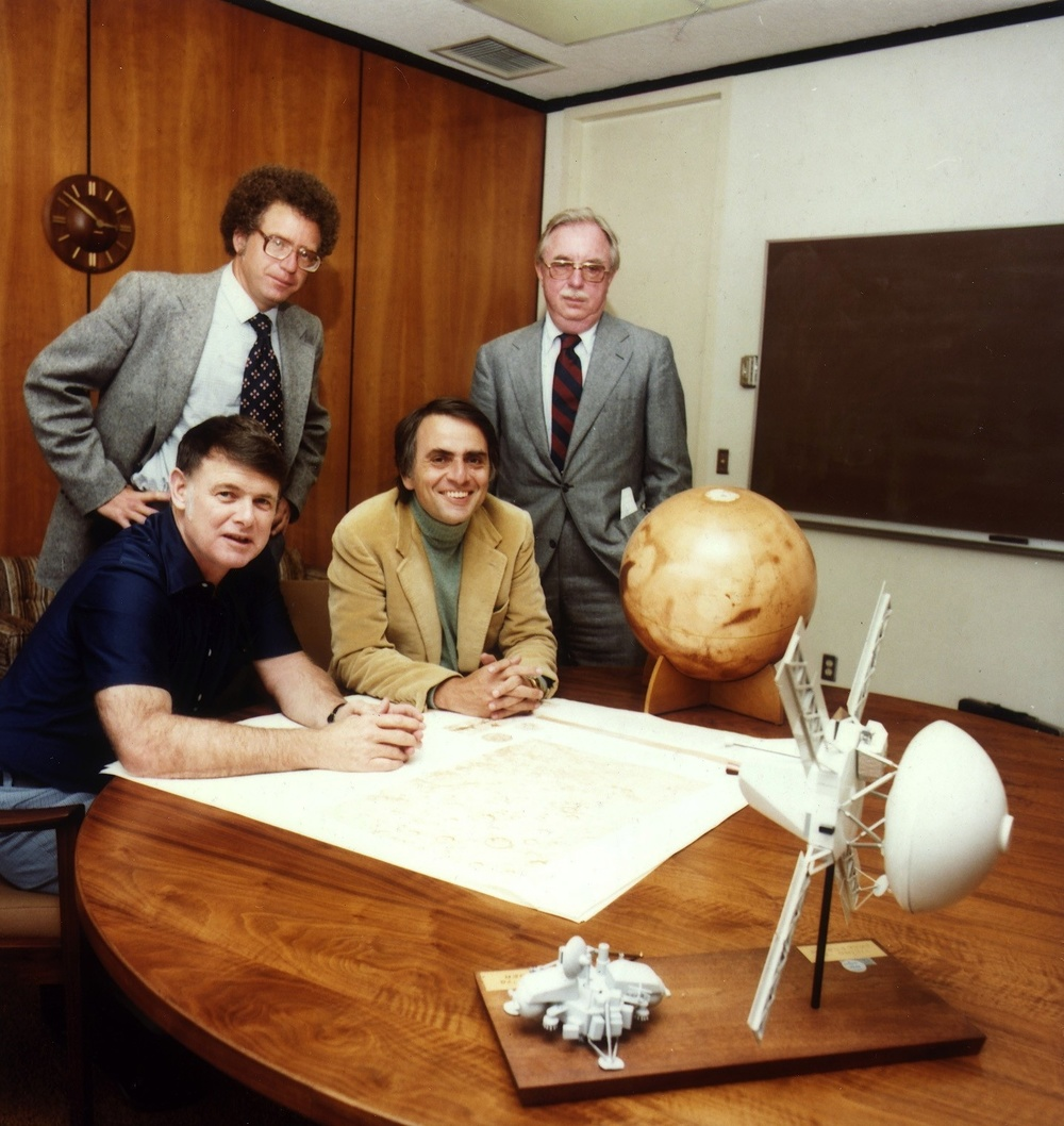 Click photo to download. Caption: Carl Sagan (sitting, in center), Bruce Murray, and Louis Friedman, the founders of The Planetary Society, at the signing of papers that formally incorporated the organization. Also pictured is Pulitzer Prize-winning journalist Harry Ashmore. Credit NASA JPL via Wikimedia Commons.