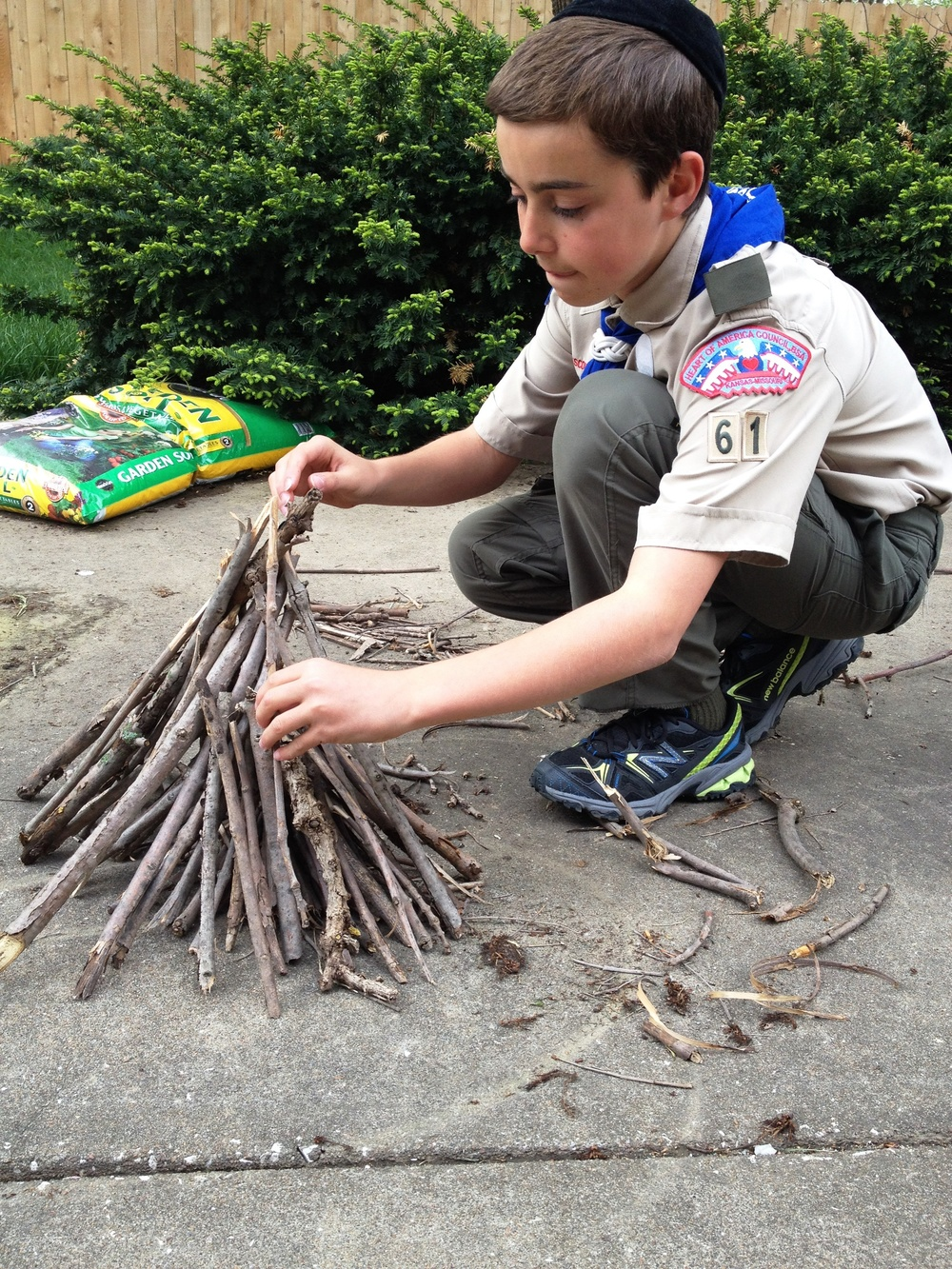 "Click photo to download. Caption: Boy Scout Abraham ""Avi"" Brudoley makes a bonfire. Pictured is step three: strengthen your structure. Credit: Maayan Jaffe."