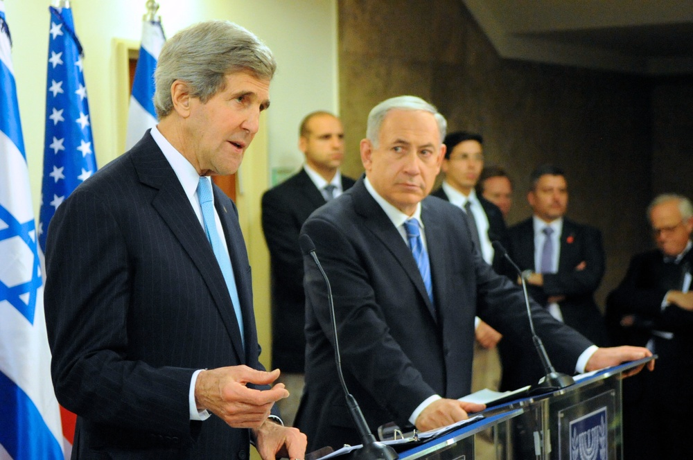 "Click photo to download. Caption: Israeli Prime Minister Benjamin Netanyahu looks on as U.S. Secretary of State John Kerry addresses reporters before a series of meetings at the Prime Minister's office in Jerusalem on January 2, 2014. Kerry recently came under fire for saying Israel could become an ""apartheid state"" in a two-state solution is not reached soon. Credit: State Department."