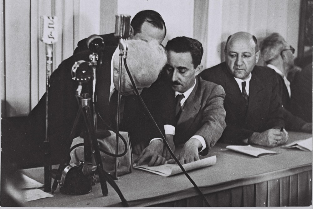 David Ben-Gurion (left) signing the Israeli Declaration of Independence, held by Moshe Sharet with Eliezer Kaplan looking on, at the Tel Aviv museum on Rothschild Blvd. on May 14, 1948. Credit: GPO.