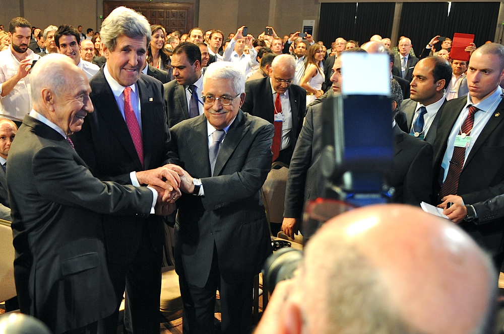 Israeli President Shimon Peres, U.S. Secretary of State John Kerry, and Palestinian Authority President Mahmoud Abbas join in a handshake at the beginning of their three speeches at the World Economic Forum in Dead Sea, Jordan, on May 26, 2013. Credit: State Department.