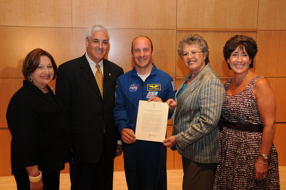 Click photo to download. Caption: On August 18, 2010, the 2006 proclamation from President George W. Bush that created Jewish American Heritage Month (JAHM) is presented by NASA astronaut Dr. Garrett E. Reisman (center) to Marcia Jo Zerivitz (second from right), founding executive director of the Jewish Museum of Florida, at a ceremony at the National Museum of American Jewish History in Philadelphia. In May 2010, the JAHM proclamation traveled 4,879,978 miles with 186 orbits of the earth aboard the U.S. space shuttle Atlantis. Credit: Courtesy Marcia Jo Zerivitz and Garrett Reisman.