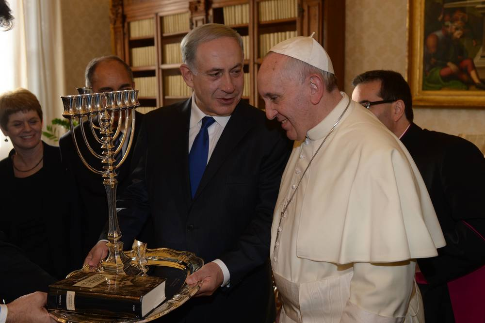 Click photo to download. Caption: Israeli Prime Minister Benjamin Netanyahu (left) presents Pope Francis with a menorah during their meeting at the Vatican on December 2, 2013. Pope Francis will visit Israel, Jordan, and the West Bank from May 24-26. Credit: Amos Ben Gershom/GPO/Flash90.