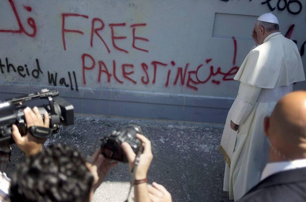 "Pope Francis prays next to graffiti that reads ""Free Palestine"" on the Israeli security fence in Bethlehem. Credit: Twitter."