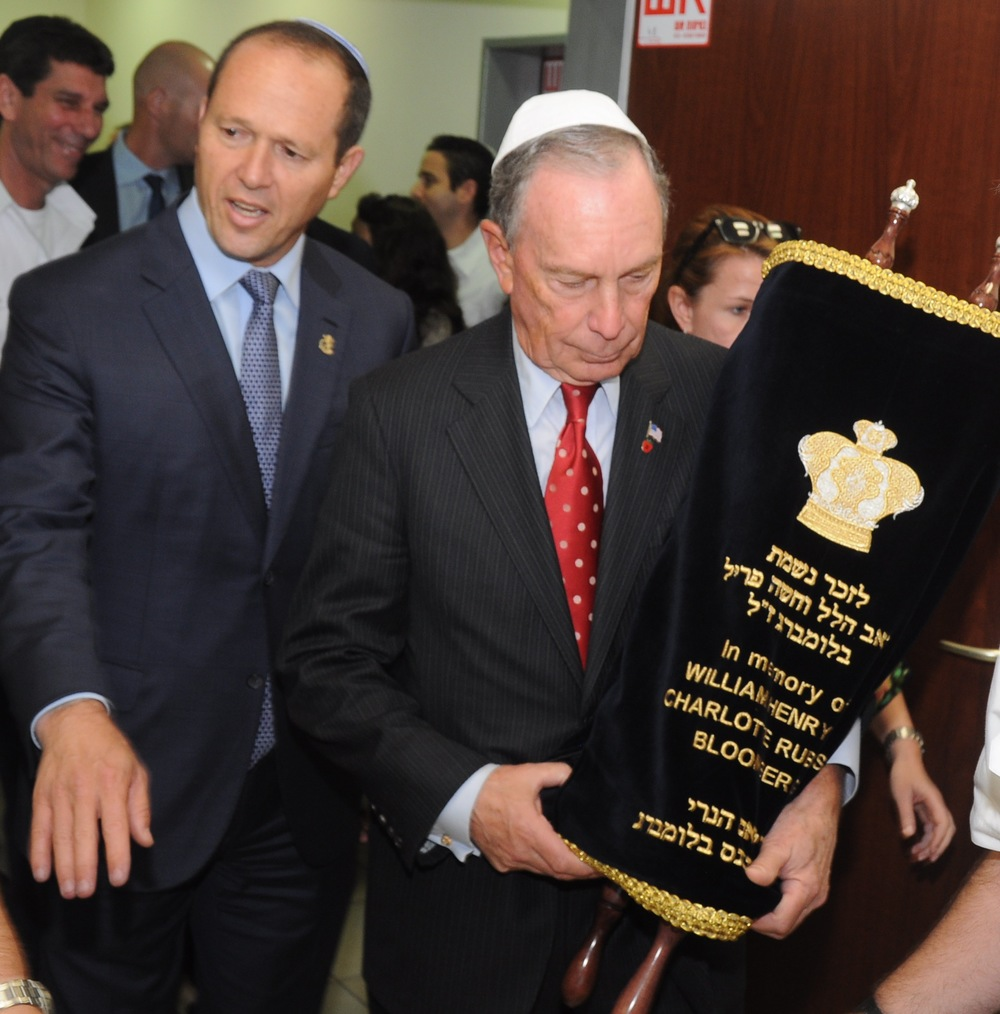 Michael R. Bloomberg (at right), mayor of New York City from 2002-2013, walks into the synagogue at the Magen David Adom Jerusalem station holding the new Torah scroll he helped dedicate in memory of his parents, William and Charlotte. Bloomberg was joined by several high-profile guests, including Jerusalem Mayor Nir Barkat (at left). Credit: Magen David Adom.