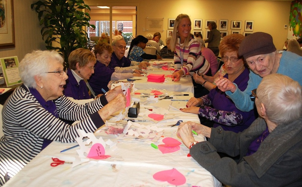 "Click photo to download. Caption: ""Chesed Corps"" volunteers of the Cedar Village Retirement Community in Mason, Ohio, create paper snowflakes in January 2013 to send to Sandy Hook Elementary School students in Connecticut. The snowflakes helped to welcome the students back to school after the shootings. Credit: Cedar Village Retirement Community."