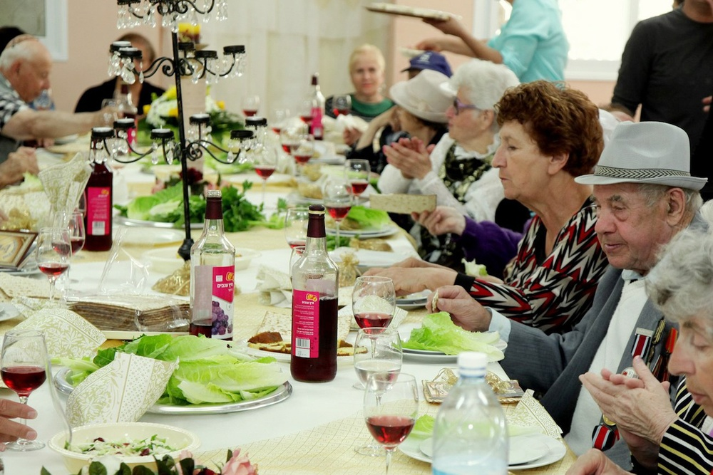 Click photo to download. Caption: Senior citizens enjoy a Passover-themed meal during the week before the holiday in the southern Israeli town of Sderot on April 10, 2014. The most common way to grow old in Israel today is to live with a foreign caretaker, says Yaron Bengera, vice president of Yad Beyad, a Tel Aviv-based agency that recruits foreign workers. Credit: Edi Israel/Flash90.