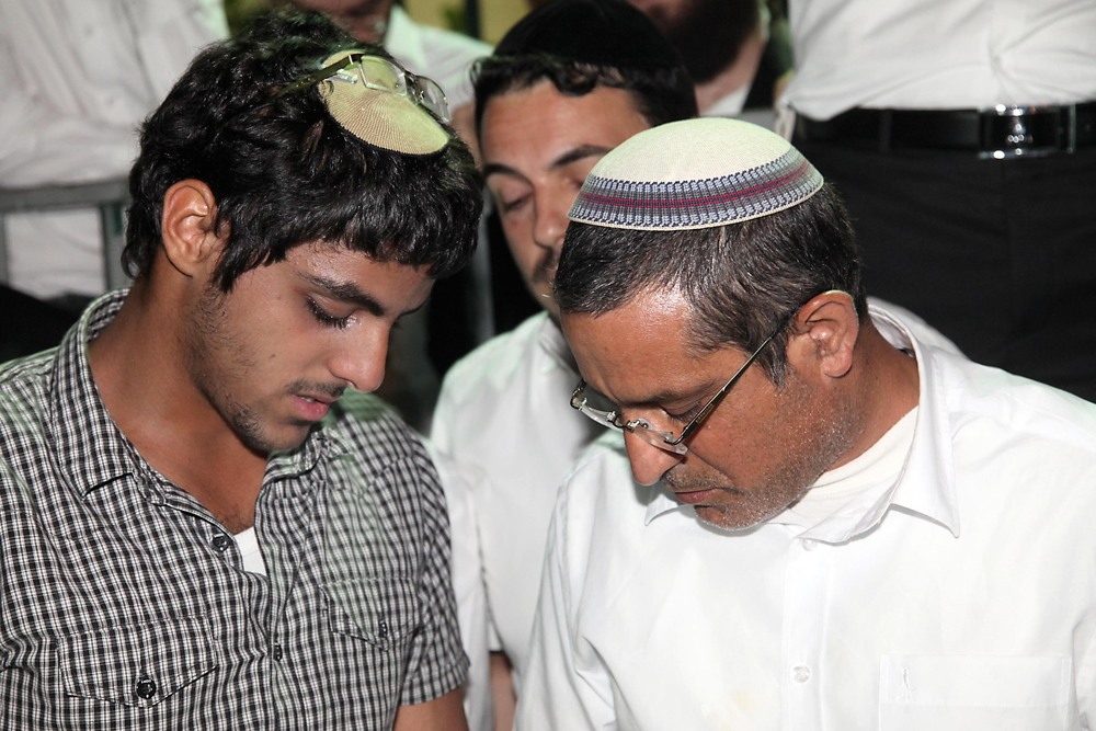 Click photo to download. Caption: Ouria Yifrach (right), father of missing Israeli teenager Eyal Yifrach, and Eyal's brother Assaf pray alongside hundreds for the safety of Eyal on June 14, 2014. Credit: Gideon Markowicz/Flash90.