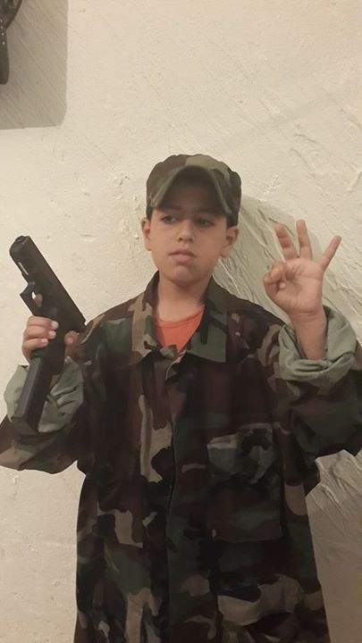 "An Arab child in military fatigues with a gun does the ""three Shalits"" salute. Credit: Facebook screenshot."