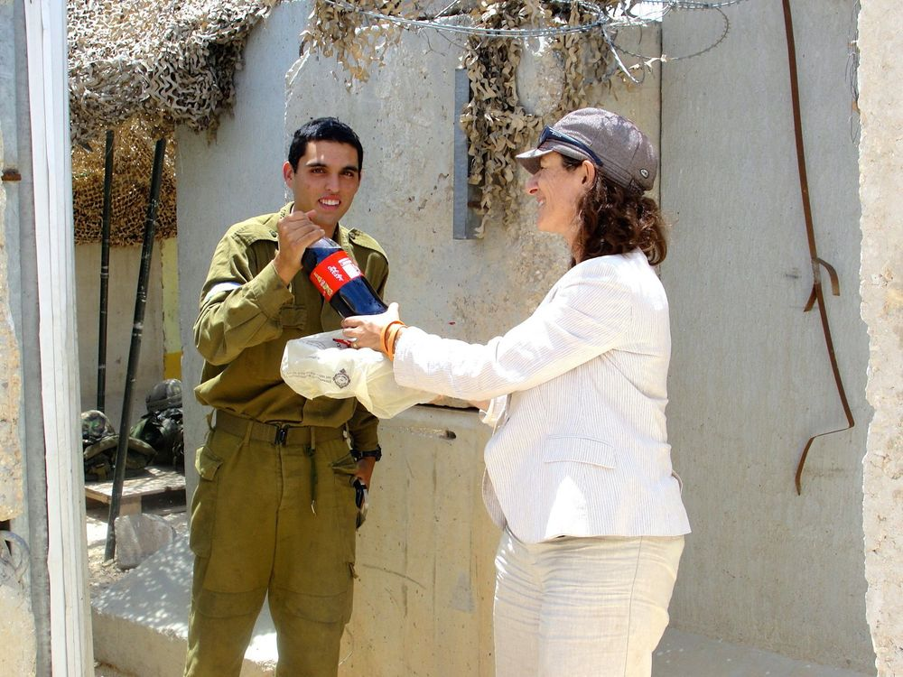 Click photo to download. Caption: Women in Green co-chair Nadia Matar delivers snacks to an Israeli soldier at Shdema. Credit: Judy Lash Balint.
