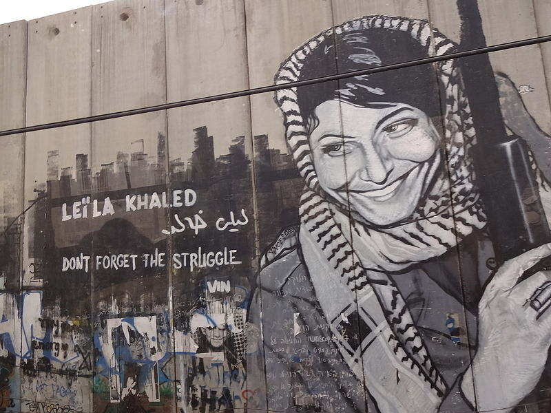 Click photo to download. Caption: The Israeli security fence in Bethlehem is pictured here painted with graffiti depicting Popular Front for the Liberation of Palestine terrorist Leila Khaled. Rabab Abdulhadi, a professor at San Francisco State University, met with Khaled on a trip funded by the state of California. Credit: Bluewind via Wikimedia Commons.