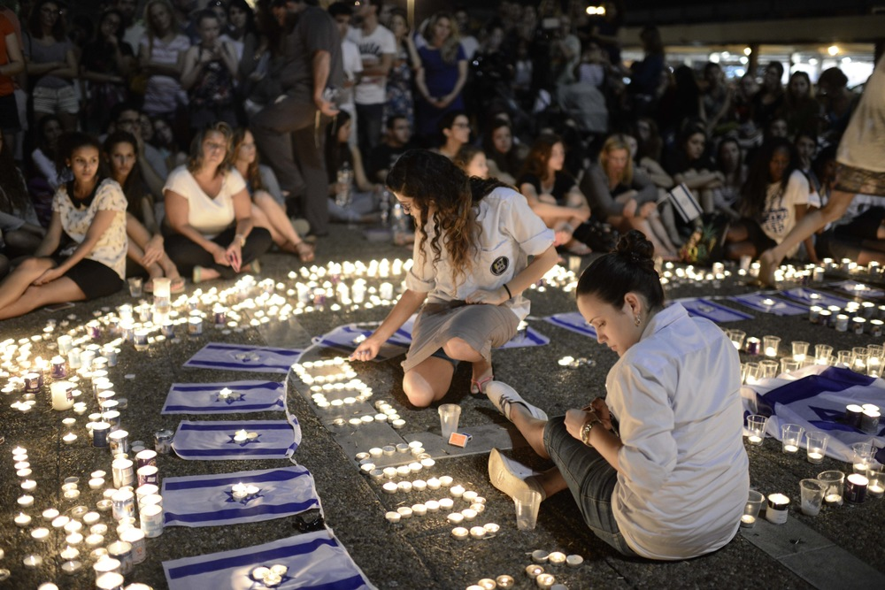 Click photo to download. Caption: Israelis light candles in Tel Aviv's Rabin Square on Monday as they mourn the news of the death of three abducted Jewish teenagers. Israeli forces found the bodies of the three missing teenagers on Monday after a nearly three-week-long search. Credit: Tomer Neuberg/Flash90.