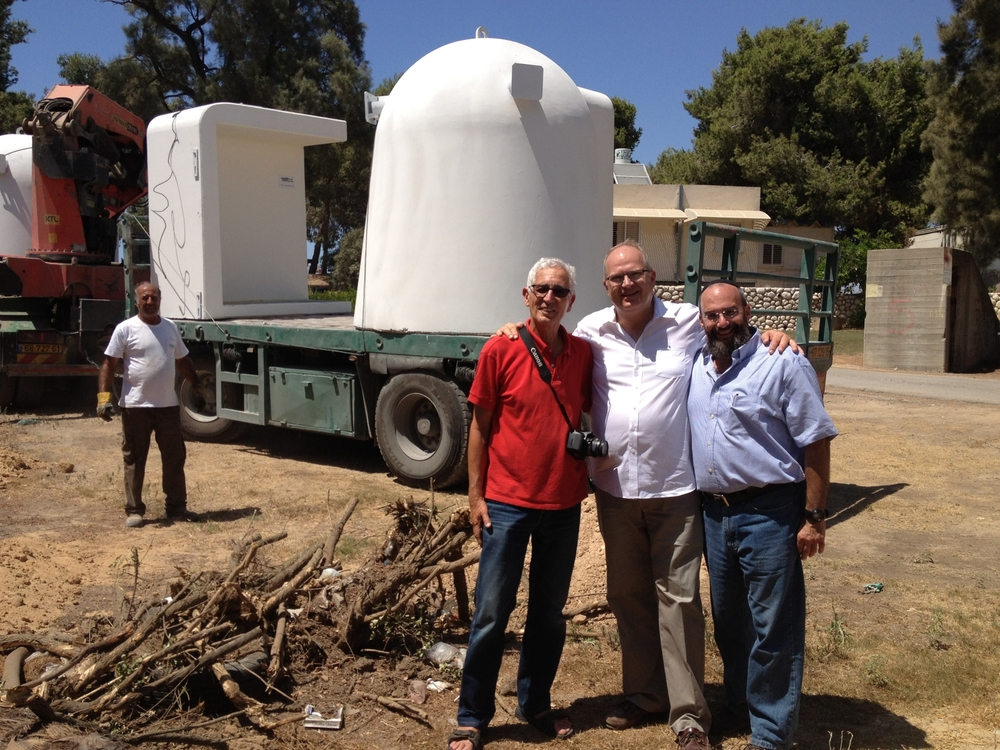 ICEJ executive director Dr.Jürgen Bühler (center), former MK Shai Hermesh (left), and Operation Lifeshield director Shmuel Bowman pictured with the delivery of one of the mobile bomb shelters in Kfar Aza. Credit: ICEJ.
