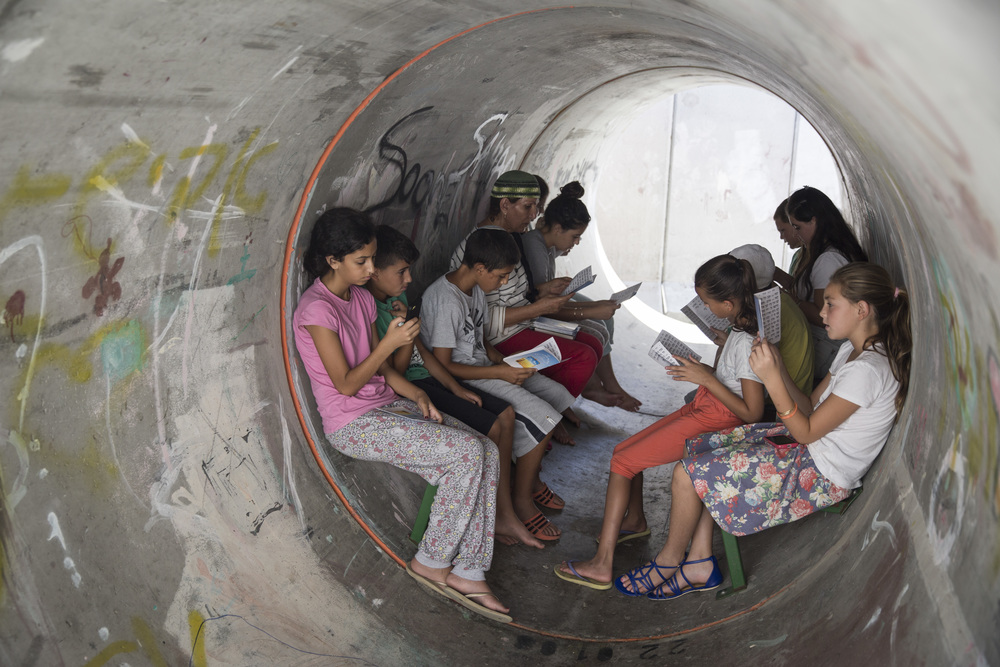 Click photo to download. Caption: On July 11, the fourth day of Operation Protective Edge, Israelis in the southern town of Nitzan sit and pray together inside a street-level bomb shelter in anticipation of a code red siren for incoming rockets. Credit: Hadas Parush/Flash90.