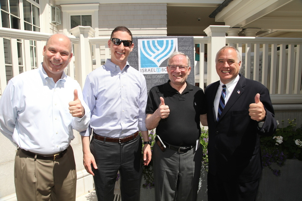 Caption: Giving a thumbs up to investing in Israel Bonds, from left to right: Stuart Garawitz, vice president for sales at the Development Corporation for Israel/Israel Bonds; Josh Mandel, Ohio's state treasurer; Izzy Tapoohi, president & CEO, Development Corporation for Israel/Israel Bonds; and Tom DiNapoli, New York's state comptroller. Mandel and DiNapoli, who combined have invested more than $200 million in Israel Bonds for their respective state portfolios, spoke as part of an Israel Bonds/Hampton Synagogue weekend on July 6. Credit: Richard Lobell.