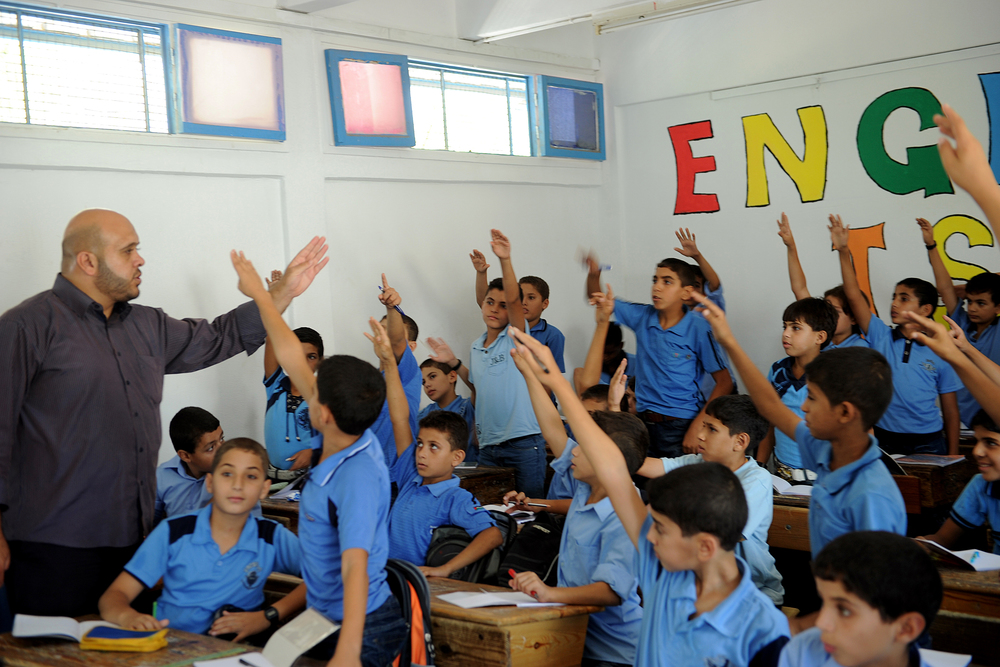 Palestinian boys raise their hands during one of the first classes of the 2011-12 academic year at a school in Gaza supported by the United Nations Relief and Works Agency for Palestine Refugees in the Near East (UNRWA). Credit: UN Photo/Shareef Sarhan.