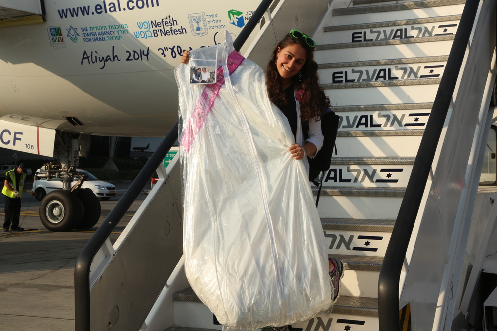 Click photo to download. Caption: Ilana Barta of Teaneck, N.J., arrives in Israel with her wedding dress. Barta, after making aliyah July 22, will get married in August. Credit: Sasson Tiram.