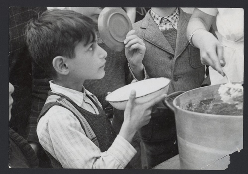 Click photo to download. Caption: In 1943, the pictured young refugee who fled Nazi-occupied France to Switzerland through the Alps receives food in a JDC-supported facility. He was then sent to a children's home, also supported by JDC. The photo is among the items featured in JDC's exhibit at the New York Historical Society. Credit: JDC.