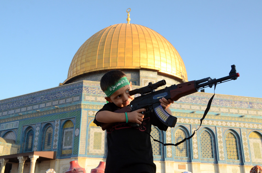 Click photo to download. Caption: A Palestinian child wearing a Hamas headband aims a toy gun during a rally after Eid prayers at the Al-Aqsa Mosque in Jerusalem on July 28, 2014. While such scenes are a manifestation of radical Islam, a growing number of pro-Israel Muslims are seeking an alternative path that they hope will lead to peace with the Jewish state. Credit: Sliman Khader/Flash90.